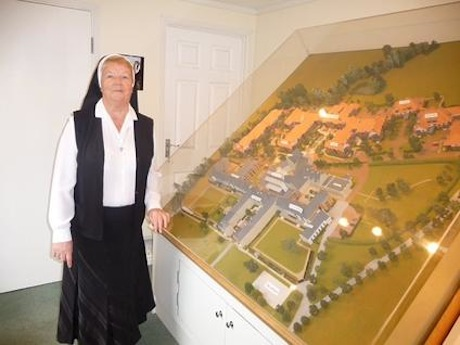 Sœur Mary Thomas devant la maquette du St. George's Park Retirement Village